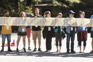 A group of young Jewish adults hold pages of the torah